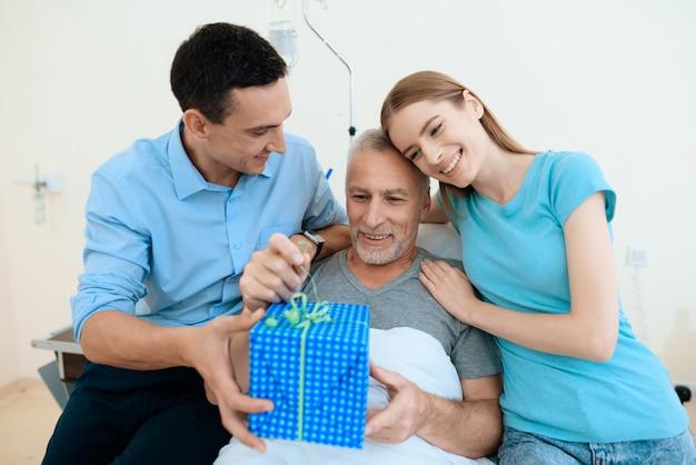 Jonge mensen brachten de oude man een geschenk in een grote doos en omhelzen hem