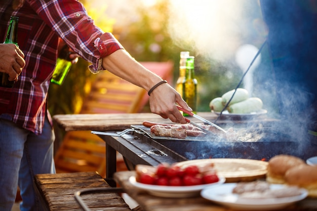 Jonge mensen die barbecue bij de grill in plattelandshuisje roosteren.