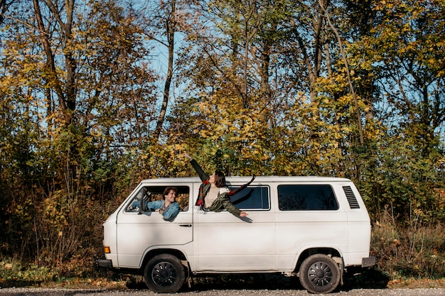 Jonge mensen die een roadtrip maken in een wit busje