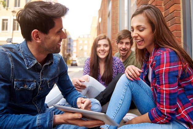 Jonge mensen die op de stoep zitten