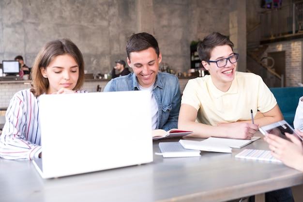 Jonge mensen die op laptop werken