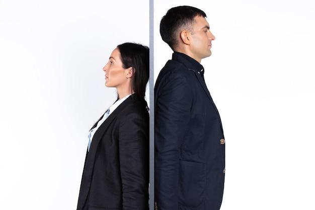Jonge mensen ernstige onderneemster en zakenman die rijtjes tegen een muur op een wit zijn