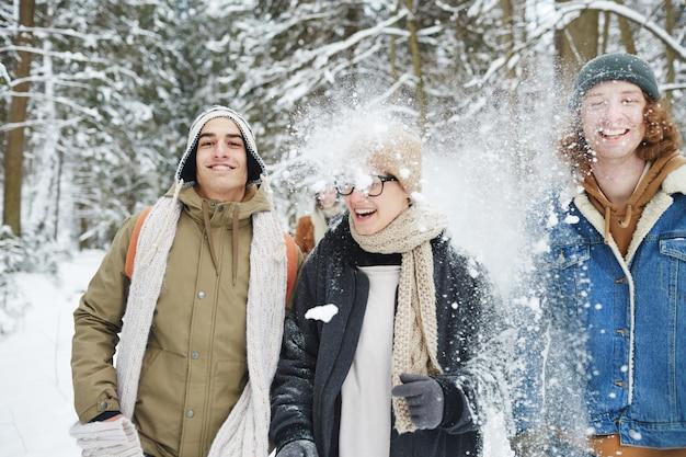 Jonge mensen in besneeuwde bossen