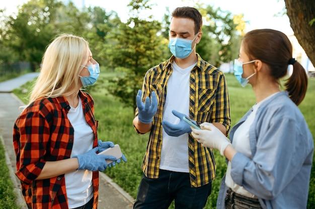 Jonge mensen in maskers en handschoenen vrije tijd in park, quarantaine. vrouwelijke persoon wandelen tijdens de epidemie, gezondheidszorg en bescherming, pandemische levensstijl