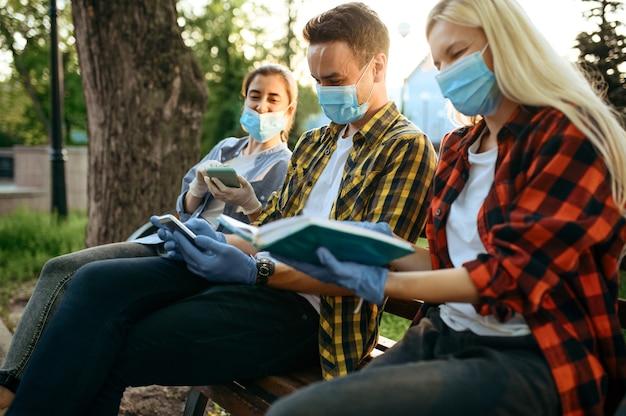 Jonge mensen in maskers zittend op een bankje in het park, quarantaine