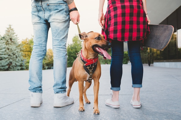 Jonge mensen in stedelijke scène lopen de hond. jonge man met een hond aan de leiband en jonge vrouw met een skateboard buitenshuis - concept van jeugdcultuur mensen die verantwoordelijk zijn en een huisdier hebben