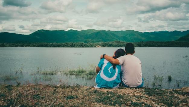 Jonge mensen kijken naar de waterkant bekijken bergen en rivieren, natuurlijke sfeer.
