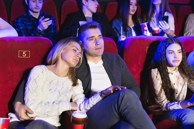 Jonge mensen kijken naar een saaie film in de bioscoop, vrouw slaapt