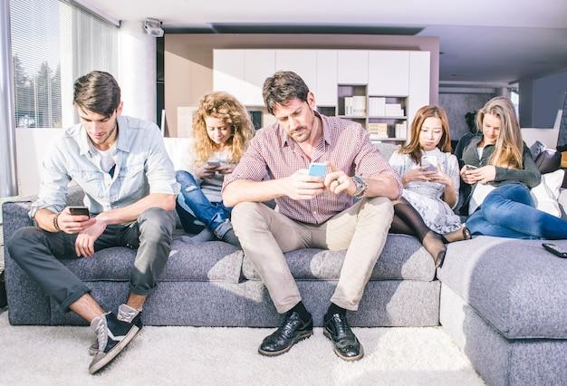 Jonge mensen kijken neer op mobiele telefoon