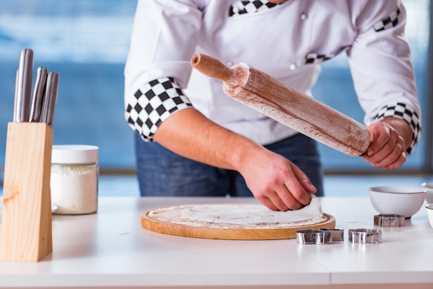 Jonge mensen kokende koekjes in keuken