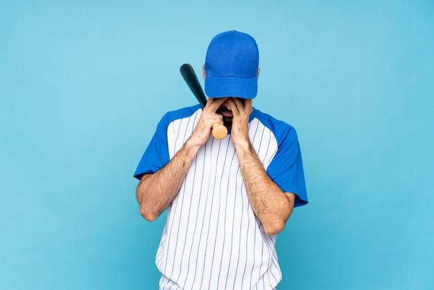 Jonge mensen speelhonkbal over geïsoleerde blauwe muur met vermoeide en zieke uitdrukking