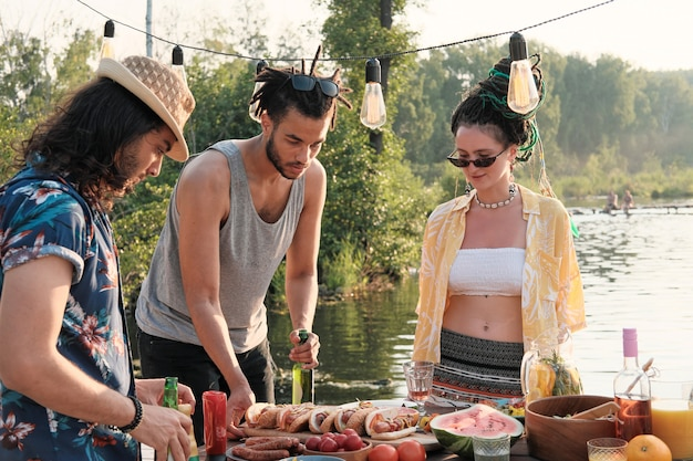 Jonge mensen staan in de buurt van de eettafel en eten hotdogs tijdens een picknick op de natuur