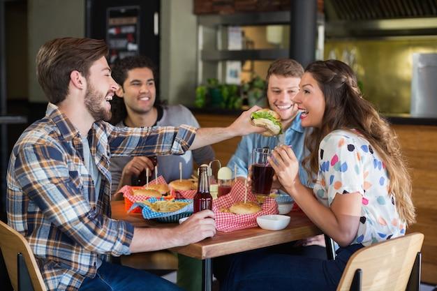 Jonge mensen voedende hamburger aan vriend in restaurant