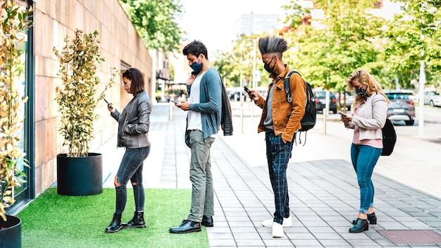 Jonge mensen wachten in de rij die sociaal afstand nemen bij stadswinkel