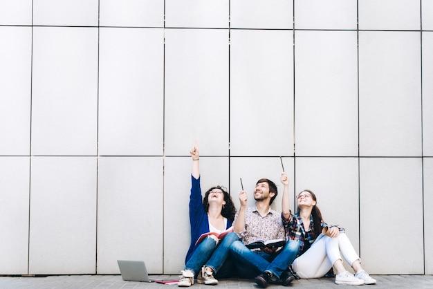 Jonge mensen zien op een vrije ruimte voor tekst, lachend en zitten in de buurt van de muur. studenten studeren. onderwijs social media concept.