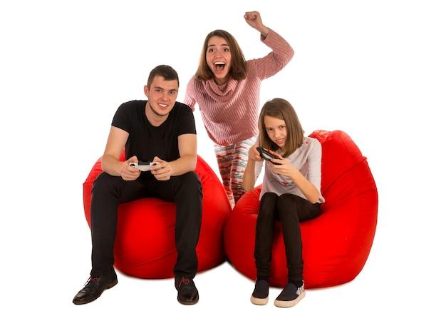 Jonge mensen zijn enthousiast over het spelen van videogames terwijl ze op rode zitzakken zitten die op wit worden geïsoleerd
