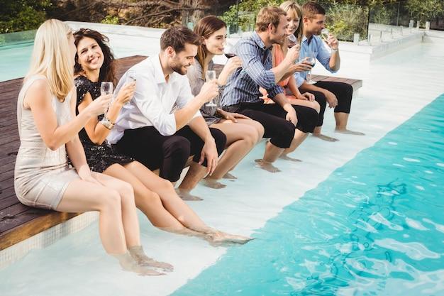 Jonge mensen zitten bij het zwembad, drinken, plezier maken, genieten van vakantie