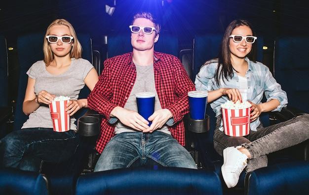 Jonge mensen zitten in stoelen in de bioscoop. ze dragen een bril om films te kijken. de kerel heeft een kop cola terwijl de meisjes een mandje popcorn hebben. ze kijken naar films. blond meisje kijkt.