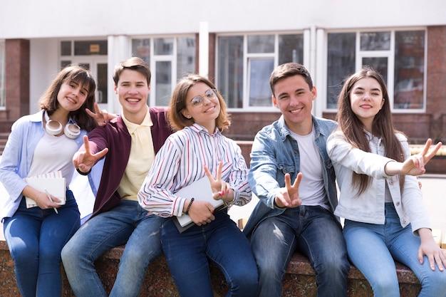 Jonge mensen zitten met boeken en twee vingers gebaren