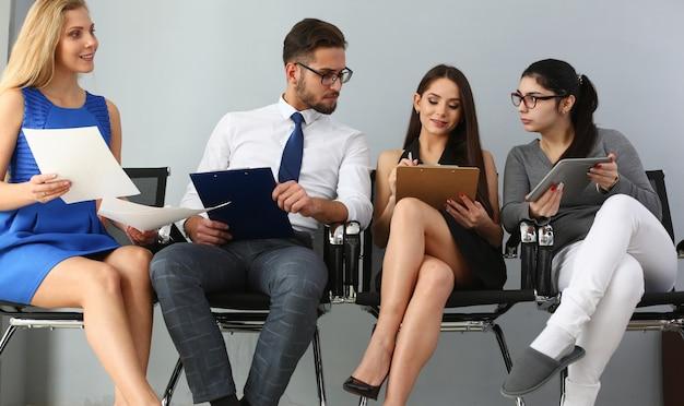 Jonge mensen zitten op stoelen gieten rij bij baas receptie