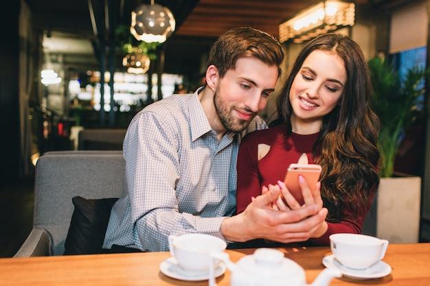 Jonge mensen zitten samen in een café en kijken naar de telefoon. ze zien er gelukkig en kalm uit.