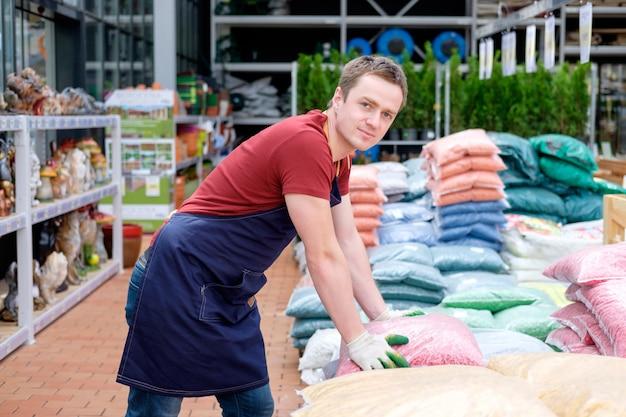 Jonge mensenarbeider in de serre van de installatiemarkt op het werk