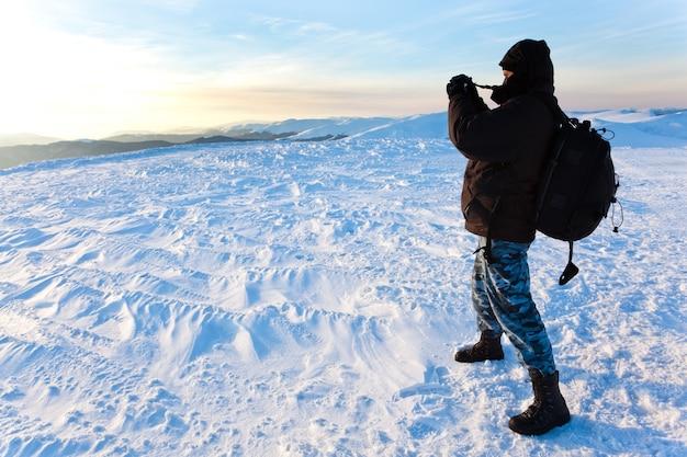 Jonge mensenfotograaf in de winterkleding die en foto bevinden zich maken