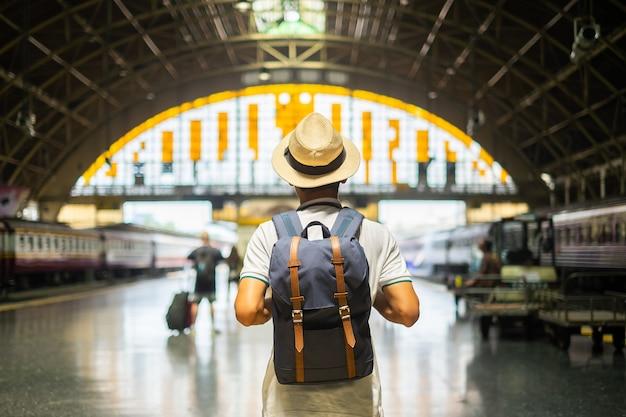 Jonge mensenreiziger die met rugzak op trein wachten