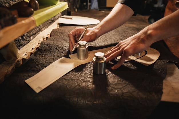 Jonge mensenschoenmaker op schoeiselworkshop.