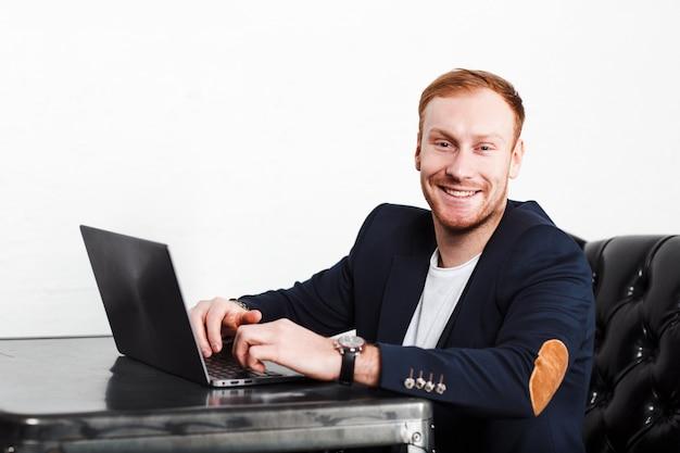 Jonge mensenschrijver in een kostuum die bij laptop en het glimlachen typen