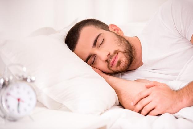 Jonge mensenslaap in comfortabel bed thuis.