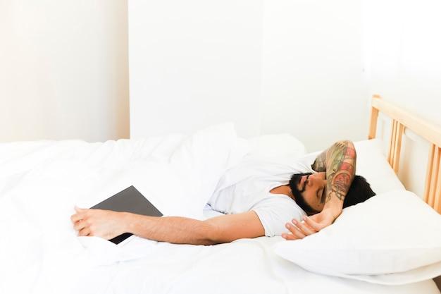Jonge mensenslaap op bed met digitale tablet