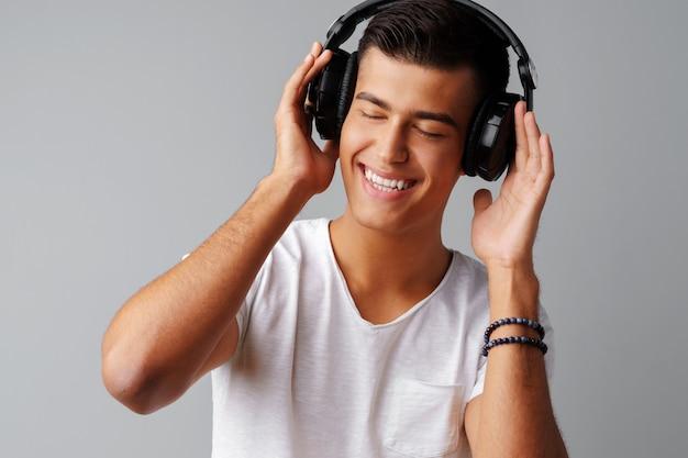 Jonge mensentiener die aan muziek met zijn hoofdtelefoons over een grijze achtergrond luisteren