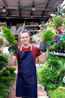 Jonge mensenverkoper in de serre van de installatiemarkt op het werk