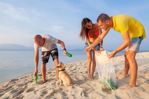 Jonge mensenvrienden halen afval en vuilnis op op een tropisch strand en redden de planeet en de ecologie in indonesië, thailand en de filippijnen