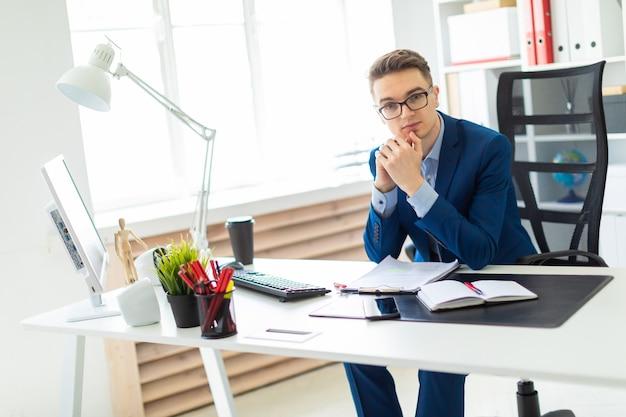 Jonge mensenzitting bij bureau in bureau en het werken met documenten.