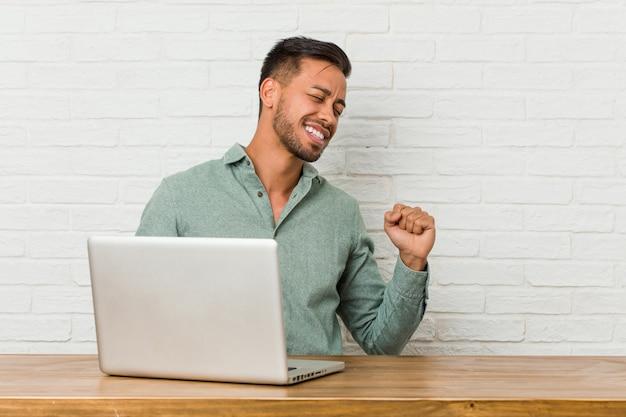 Jonge mensenzitting die met zijn laptop werkt en pret danst heeft.