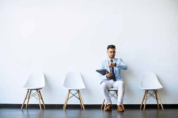 Jonge mensenzitting in de wachtkamer met een in hand omslag en het controleren van tijd vóór een gesprek