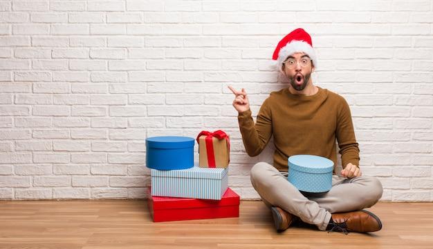 Jonge mensenzitting met giften die kerstmis vieren die aan de kant richten