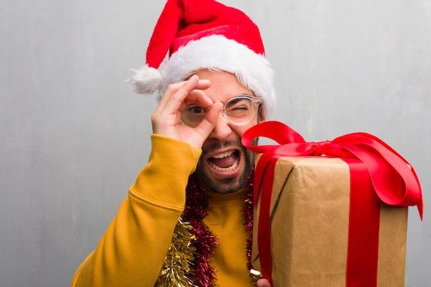 Jonge mensenzitting met giften die kerstmis vieren die het gebaar van een kijker maken