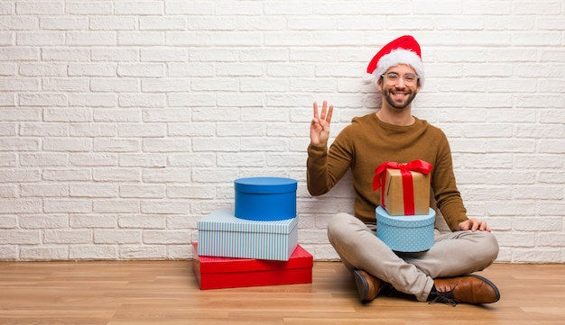 Jonge mensenzitting met giften die kerstmis vieren die nummer drie tonen