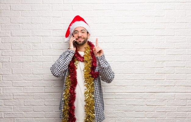 Jonge mensenzitting met giften die kerstmis vieren die nummer één tonen