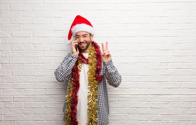 Jonge mensenzitting met giften die kerstmis vieren die nummer twee tonen