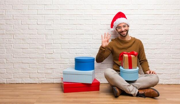 Jonge mensenzitting met giften die kerstmis vieren die nummer vier tonen