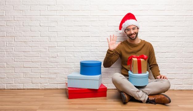 Jonge mensenzitting met giften die kerstmis vieren die nummer vijf tonen