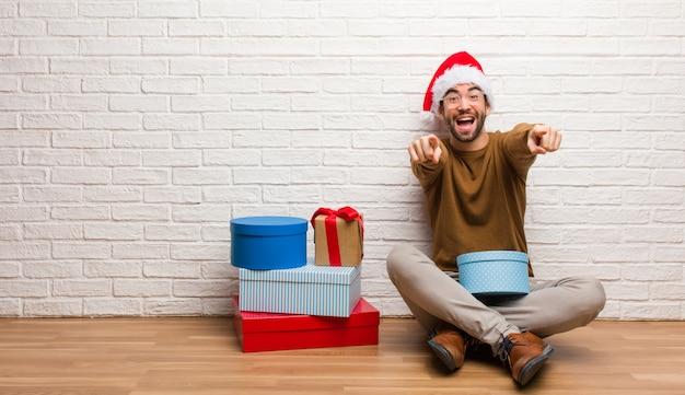 Jonge mensenzitting met giften die vrolijke kerstmis vieren en glimlachen