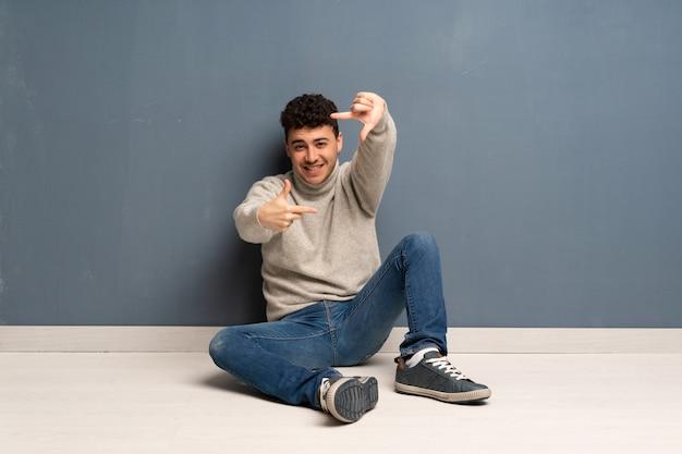 Jonge mensenzitting op de vloer die gezicht concentreert. framing symbool