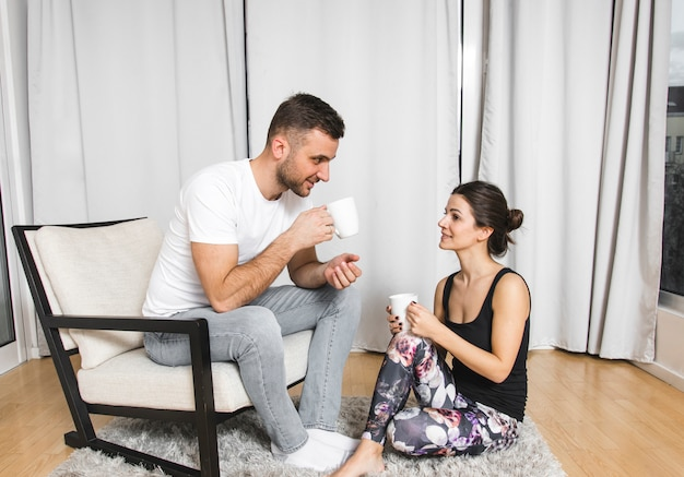 Jonge mensenzitting op stoel met haar meisje die de koffie thuis drinken