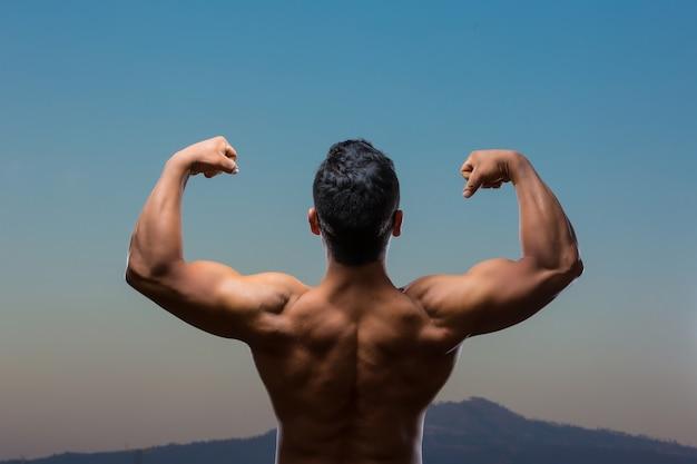 Jonge mexicaanse bodybuilder rugspieren poseren buitenshuis