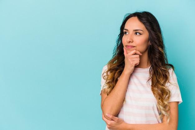 Jonge mexicaanse die vrouw op blauwe achtergrond wordt geïsoleerd die zijwaarts met twijfelachtige en sceptische uitdrukking kijkt.